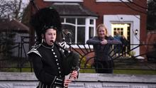 George Orchin, 12, from the Campbell College Pipe Band, plays Amazing Grace outside his neighbour's Jill Scott's house in East Belfast (PA)