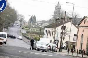A police officer stands where Main street and high street, Newtownbutler meet with the Church of the immaculate Conception and St. Mary's Primary school in the distance beyond