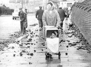 A mother and her pram negotiate the rubblestrewn streets of Ballymurphy in June 1970