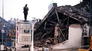 The Cenotaph at Enniskillen with the devastated community centre in the background. Credit: PA