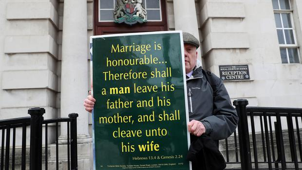 A man holds a placard quoting the Bible outside the Royal Courts of Justice in Belfast (Brian Lawless/PA)