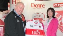 Hugh McWilliams and his wife Anne with a Derry GAA jersey featuring the H&A Mechanical Services logo