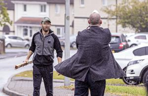 A plain clothes detective draws his pistol and takes aim at a male attempting to attack police at the scene of a security operation in the Glenbawn Avenue area of west Belfast