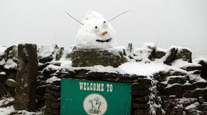 """A snowman's head above a """"Welcome To Middleton-in-Teesdale"""" sign in County Durham."""
