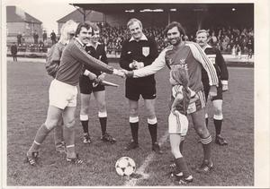 George shakes hands with the Glenavon captain Alan Frazer and referee Malcolm Moffatt