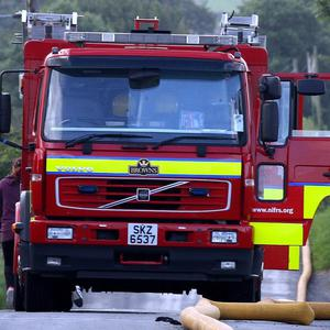 A firefighter has died after tackling a car fire in Lurgan