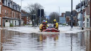 Emergency workers use a boat in floodwater on Warwick Road in Carlisle to rescue a resident