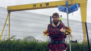 Alex Ellis-Roswell outside the Harland and Wolff shipyard in Belfast as he completed the 2,500-mile Irish leg of his journey around the entire coastline of Britain and Ireland