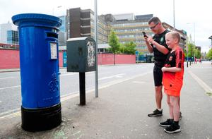 Paul Moore, a cleaner at the Royal Victoria Hospital, with his son Kayden Parker (10) photographs a post box on the Falls Road