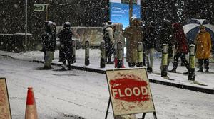 People cross a bridge over the River Mersey as snow falls in East Didsbury, Manchester, where homes are being evacuated (Peter Byrne/PA)