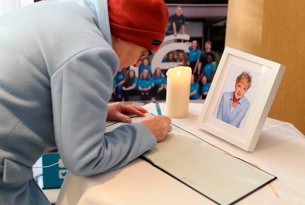 A woman signs a book of condolence at RTE Radio Centre in Donnybrook, Dublin, for broadcaster Marian Finucane