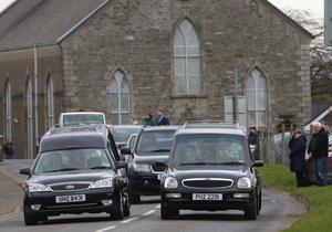 Hearses carrying William and Madge Finlay's coffins drive side by side at their funeral in Ardstraw near Newtownstewart in Co Tyrone on Saturday