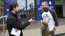 Belfast Telegraph reporter Allan Preston speaks to passenger Nigel McAlpine from Bangor outside Lanyon Place Station after travelling on a train wearing a face mask