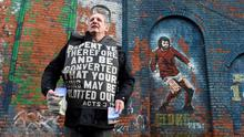 John Dumigan protests against football being played on a Sunday as he hands out leaflets beside a mural of George Best outside Windsor Park