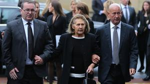 Kathleen Reynolds flanked by sons Albert and Philip at the funeral of her husband