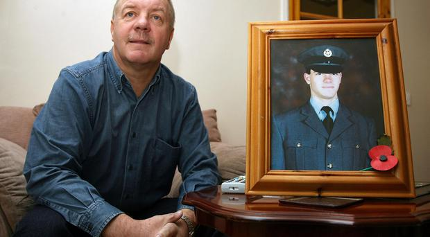 Raymond McCord with a portrait of his murdered son Raymond Jnr (Paul Faith/PA)