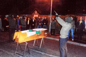 A masked gunman fires shots over the coffin of Liam Mulhern in west Belfast on Sunday night