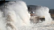 People walk along the harbour in Saltcoats in Ayrshire as high waves batter the coastline