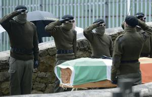 Masked paramilitaries salute beside the coffin of Tony Catney during yesterday's funeral