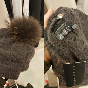 The hat with its raccoon fur pompom