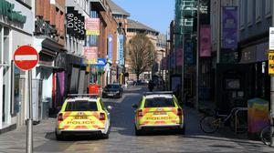 Shuttered stores and police patrols on Ann Street in Belfast, as the UK continues in lockdown to help curb the spread of the coronavirus (PA)