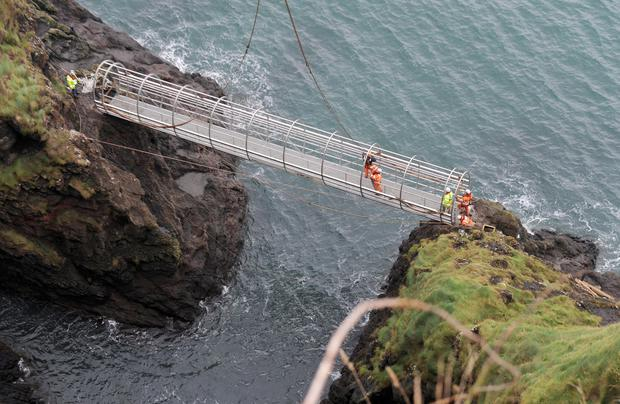 The new tubular bridge section of The Gobbins path is hoisted into place