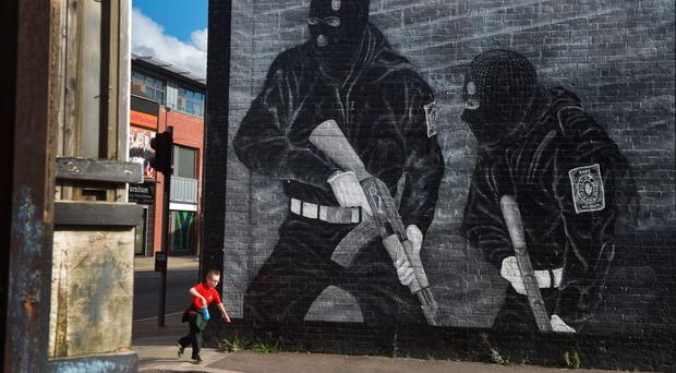 A young boy runs past a paramilitary mural in east Belfast