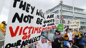 People gather outside the Dail sitting at the Convention centre in Dublin to take part in a protest calling for the full reopening of services for adults with disabilities (Brian Lawless/PA)