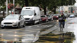 A cyclist passes slow traffic on the North Quays as new restrictions and measures prioritise buses in Dublin city