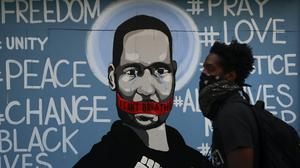 A man with a face covering walks past a mural depicting George Floyd during a protest over the death of Floyd Sunday, May 31, 2020, in Los Angeles. Floyd died in Minneapolis on May 25 after he was pinned at the neck by a police officer. (AP Photo/Jae C. Hong)