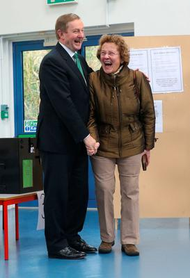 TaoiseachEnda Kenny meets a voter at a polling station at St Anthony's School in Castlebar, Co Mayo, yesterday as the Republic went to the polls in one of the most unpredictable elections in recent times