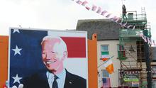 Men erect flags on top of a building as residents of Ballina, Co Mayo, Ireland, begin celebrations (PA)