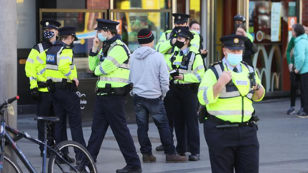 Gardai speak to a member of the public on O'Connell Street in Dublin city centre (Brian Lawless/PA)