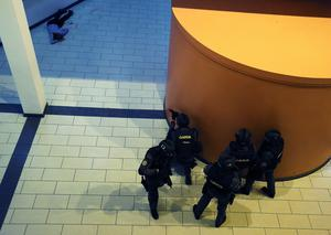 Members of the Garda Emergency Response Unit take cover as a victim lies on the floor (Brian Lawless/PA Wire)