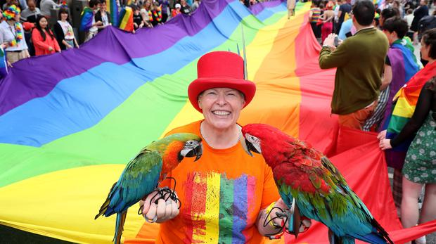 Barbara Doyle, from Coolock, with her macaw's Quinn and Rosie as they take part in the Pride parade in Dublin (Brian Lawless/PA)