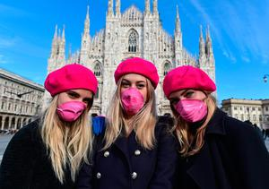 Women wearing pink protective masks pose in front of Milan Cathedral to mark International Women's Day