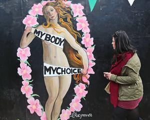 A woman passes a pro-choice mural in Dublin urging a yes vote (Niall Carson/PA)