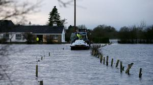 A tractor brings sandbags to a home in Carrickobrien following flooding
