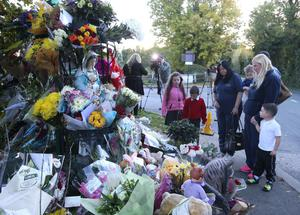 Members of the public look at flowers at the site of the tragedy