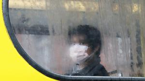 A person wearing a protective face mask sits on a bus in Dublin (Brian Lawless/PA)