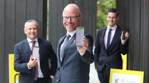 """HSE director general Paul Reid, Health Minister Stephen Donnelly and acting chief medical officer Dr Ronan Glynn launch the official Irish health service executive """"Covid Tracker"""" contact tracing app at the Department of Health in Dublin (Niall Carson/PA)."""