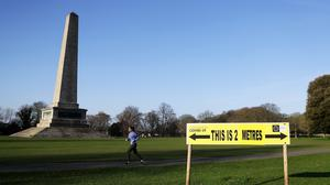 A woman runs past a sign encouraging social distancing in Dublin's Phoenix Park (Brian Lawless/PA)