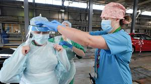 Medical staff put on their personal protective equipment ahead of a shift on the front line of the coronavirus pandmic (PA)