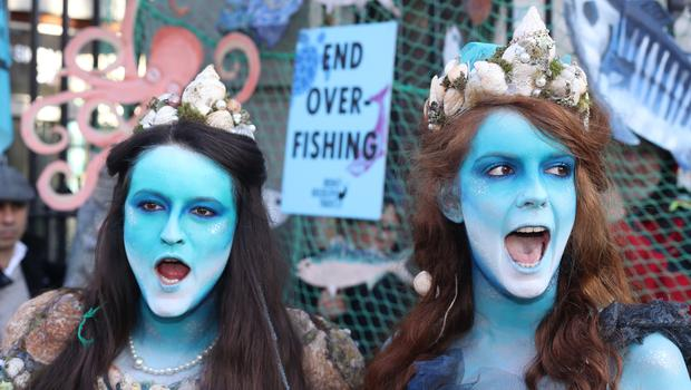 Leah Rossiter (left) and Ceara Carney dressed as mermaids during the protest (Niall Carson/PA)