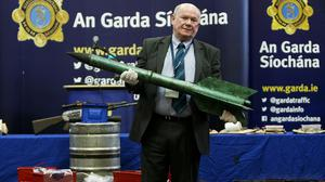 Detective Sergeant Tom Carey holds an improvised rocket in a display of samples of weapons seized during investigations into dissident republican activity