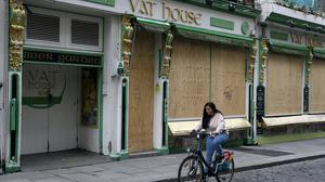 A woman cycles by a boarded up pub in the Temple Bar area of Dublin. Bars will be able to reopen on June 29th if they serve food and have table service only, as phase two of Ireland's coronavirus recovery road map comes into effect on Monday 8th June along with other measures originally envisaged for later phases.