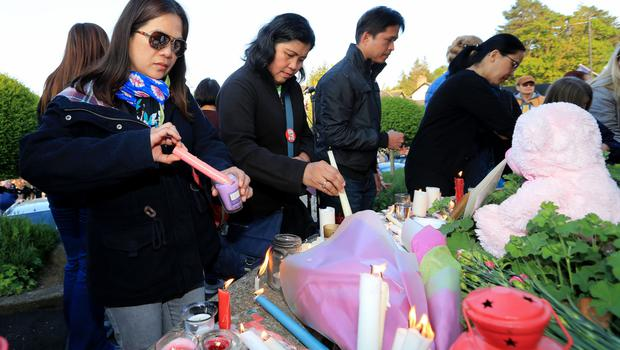 People place candles and flowers around a memorial after the vigil