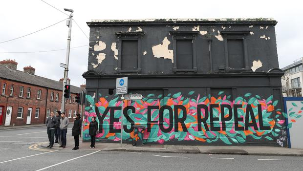 People stand beside a mural in Dun Laoghaire calling for a repeal of the Eighth Amendment of the Irish Constitution (Niall Carson/PA)