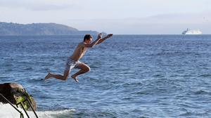 A man jumps into the sea at the Forty Foot in Sandycove, Dublin, as the bathing spot has reopened (Brian Lawless/PA)