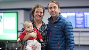 Samantha Harvey, baby Finnan MacDiarmada and Oisin MacDiarmada waiting for a United Airlines flight out of Washington DC (Niall Carson/PA)